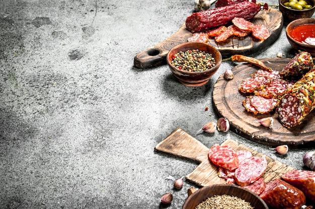 Diversi tipi di salame con spezie ed erbe aromatiche su vecchie tavole su un fondo rustico