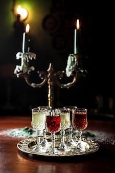 Diversi tipi di vermouth in piccoli bicchieri da liquore su un vassoio d'argento, un bellissimo vecchio candelabro con candele