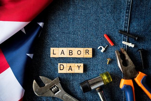 Diversi tipi su chiavi, strumenti pratici, bandiera usa e tag in legno su blue jeans.