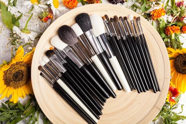 Diversi pennelli per il trucco sul piatto accanto a fiori selvatici su sfondo di legno