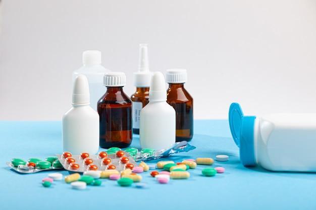 Diverse medicine mediche, siringhe, spray, flaconi di gocce, sciroppo, compresse colorate sparse, capsule