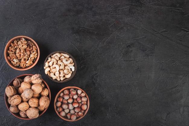 Diverse noci nei piatti, noci, nocciole, anacardi e mandorle