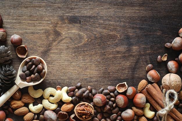 Diversi dadi su un tavolo di legno. cedro, anacardi, nocciola, noci e un cucchiaio sul tavolo. molte noci sono con guscio e chistchenyh su uno sfondo di legno