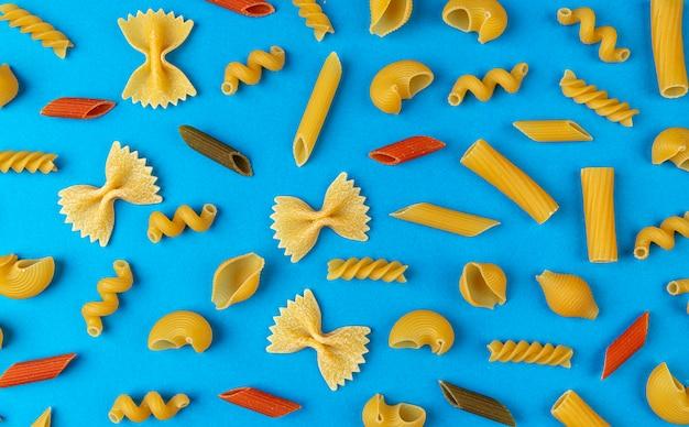Diversi tipi di pasta su blu, vista dall'alto del modello di pasta mista secca