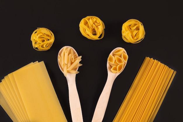 Diversi tipi di pasta in cucchiai di legno sul tavolo nero