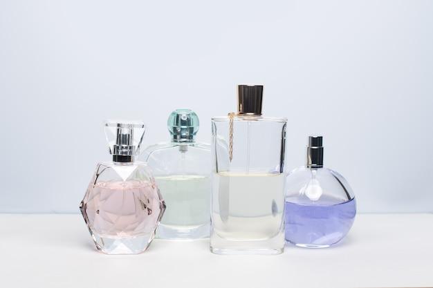Bottiglie di profumo differenti sulla superficie bianca