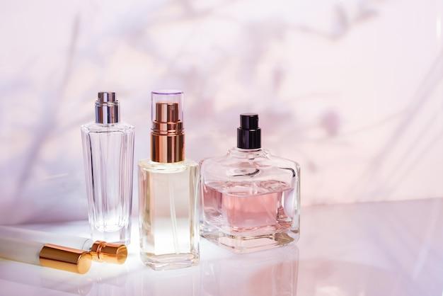 Diverse bottiglie di profumo con profumo e campioni in rosa