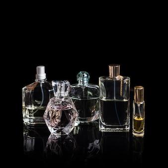 Diverse bottiglie di profumo con riflessi sulla superficie nera