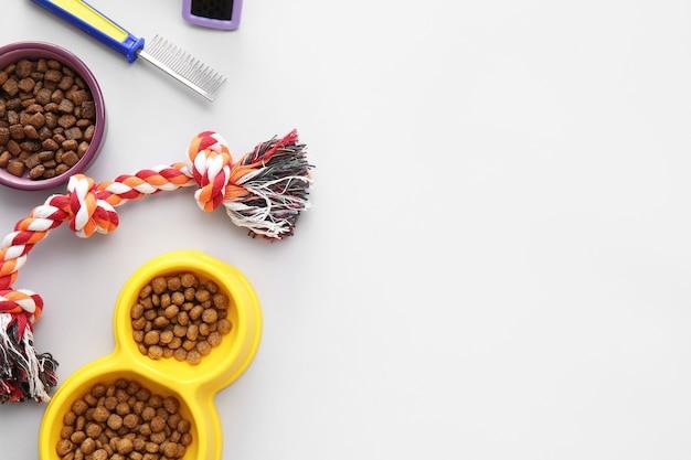 Diversi accessori per la cura degli animali domestici su sfondo chiaro