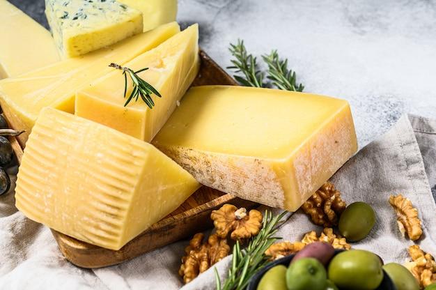 Diversi pezzi di formaggio con olive noci e uva. snack deliziosi assortiti. sfondo grigio. vista dall'alto