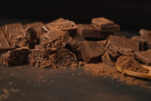 Diversi pezzi di cioccolato fondente e cacao in polvere su una superficie scura. spazio per il testo