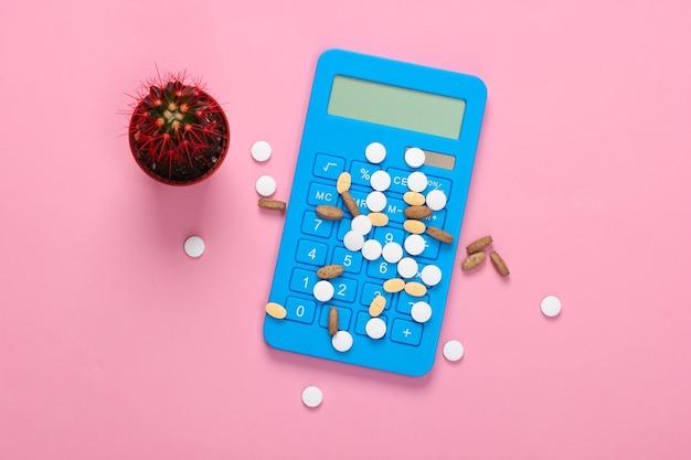 Diverse pillole e calcolatrice, cactus in rosa