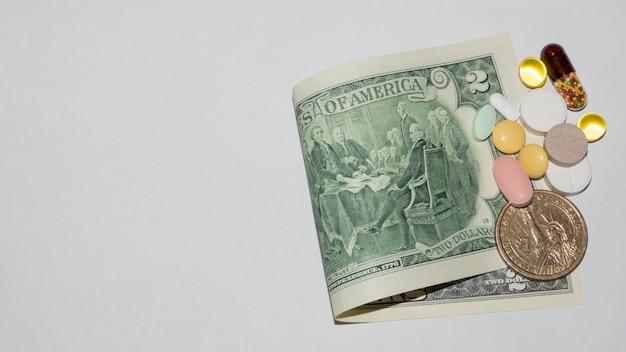 Diverse pillole sulla banconota da due dollari su sfondo bianco, vista dall'alto