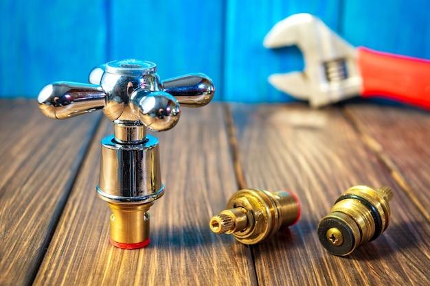 Diverse forniture idrauliche e strumenti su uno sfondo di legno e vintage blu. adatto per il sito della riparazione di prodotti idraulici.