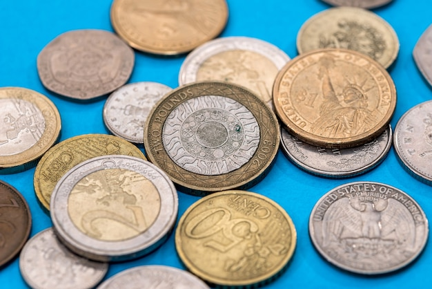 Diverse monete libbra su una superficie blu.
