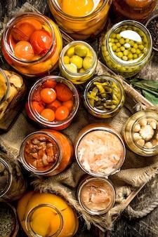 Diverse verdure conservate da verdure e funghi in barattoli di vetro sulla tavola di legno.