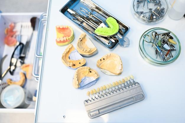 Attrezzature dentali professionali differenti, strumenti e strumenti in una clinica dell'ufficio di stomatologia dei dentisti su un fondo bianco. cast in silicone della mascella.