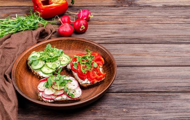 Diversi panini con cetriolo, ravanello, paprika rossa e microgreens su un piatto su una superficie di legno