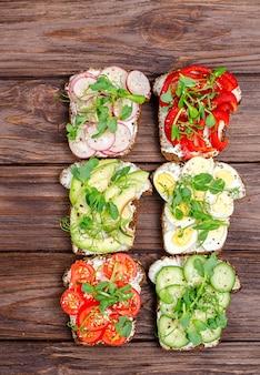 Diversi panini con verdure e microgreens su pane tostato su uno sfondo di legno. spuntino sano e piatto. vista dall'alto. orientamento verticale