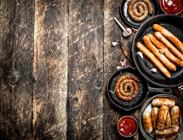 Diverse salsicce in padelle con salsa di pomodoro sulla tavola di legno.