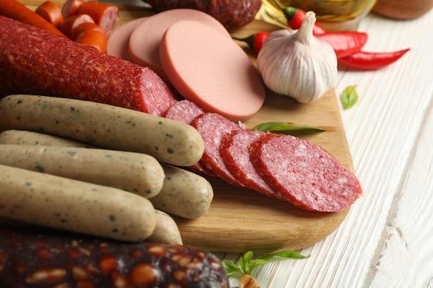 Salsiccie e spezie differenti su di legno