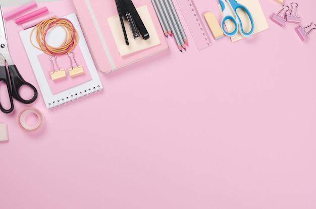 Forniture scolastiche differenti su sfondo rosa chiaro