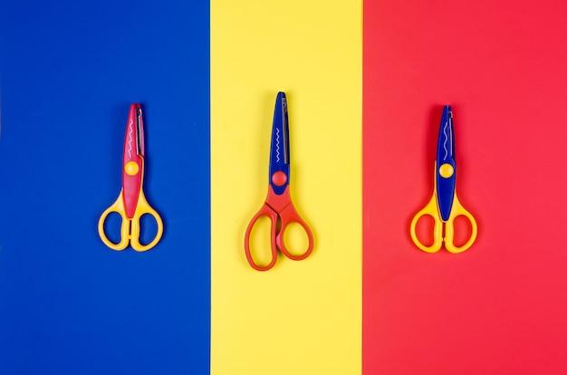 Forbici differenti per la creatività dei bambini su sfondo di carta colorata.