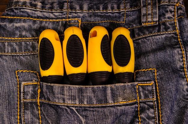 Cacciaviti diversi in una tasca dei jeans blu. vista dall'alto