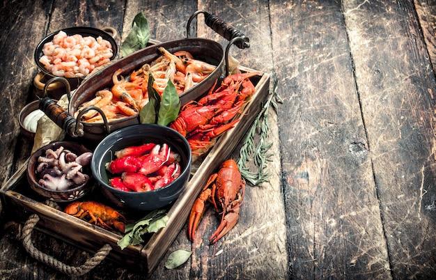 Diversi frutti di mare in ciotole. su uno sfondo di legno.