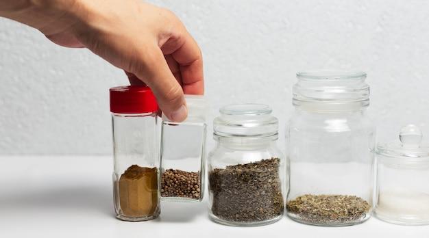 Condimento diverso in coppe di vetro, su superficie bianca.