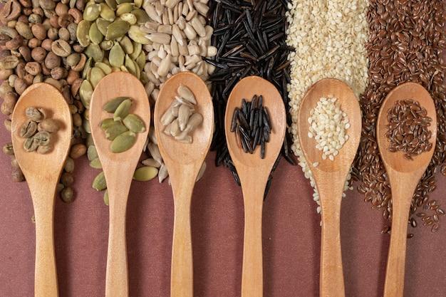 Semi differenti in cucchiai di legno su una superficie di semi differenti e marrone