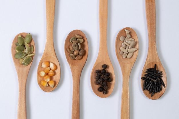 Semi differenti in cucchiai di legno su una superficie bianca
