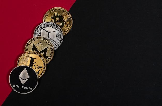 Diverse monete di valuta crittografica lucide, criptovaluta su sfondo nero e rosso con posto per il testo.