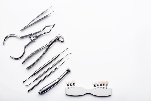 Diversi strumenti medici in metallo lucido su sfondo bianco