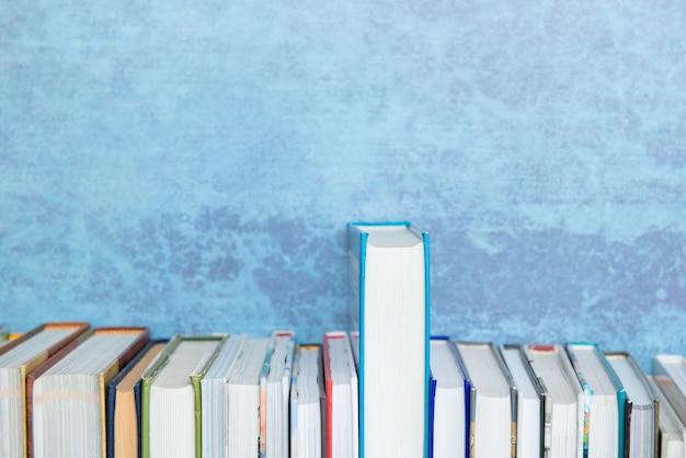 Libri di diverse dimensioni sullo scaffale per libri, priorità bassa blu. educazione, conoscenza, lettura, ritorno a scuola. un libro spicca tra gli altri, crescita, confronto, concetto di sviluppo