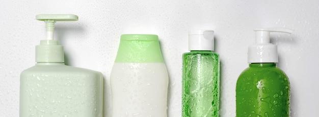 Contenitori di dimensioni e forme diverse per detergente tonico condizionatore tonico, sapone e shampoo su sfondo bianco con gocce d'acqua. prodotti di bellezza organici naturali