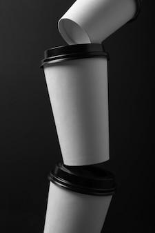 Tazze di caffè di carta bianca di diverse dimensioni con coperchio nero su sfondo nero