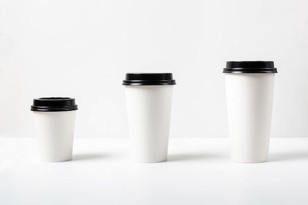 Tazze di caffè di carta bianca di diverse dimensioni con coperchio nero su sfondo bianco