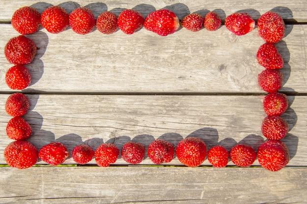 Fragole mature rosse di diverse dimensioni sono incorniciate su un tavolo di legno
