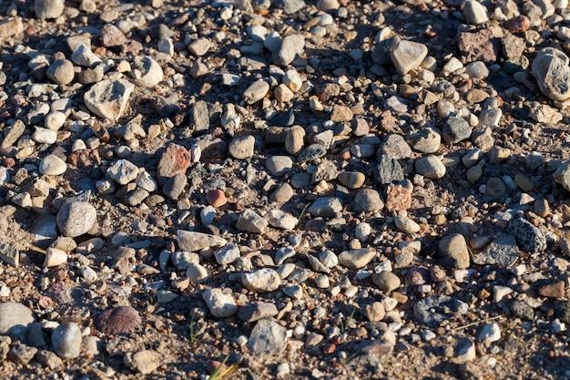 Dimensioni diverse ma tutte piccole pietre sulla strada nella sabbia