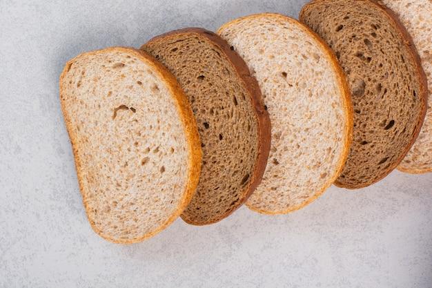 Diverse fette di pane, sul marmo.