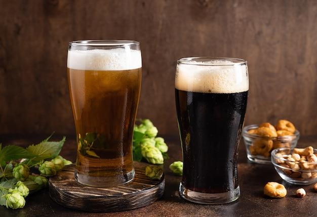 Diversi tipi di birra artigianale in bicchieri gelati e snack sul tavolo scuro concetto di birrificio di birra
