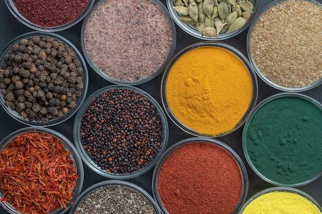 Diverse spezie ed erbe aromatiche sullo sfondo, primi piani, vista dall'alto. assortimento di spezie colorate, semi ed erbe aromatiche per cucinare