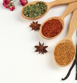 Spezie ed erbe aromatiche differenti in cucchiai di legno isolati su bianco