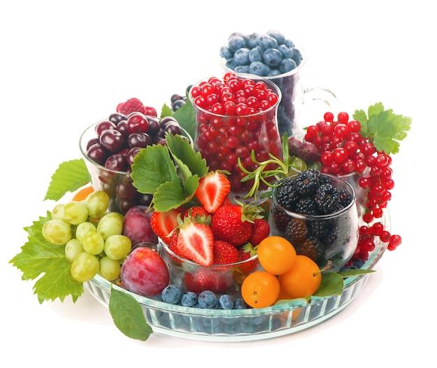 Diverse bacche estive ribes rosso, uva spina, lampone in vassoi di vetro. ordinati per tipo.