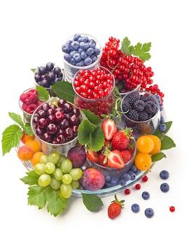 Diverse bacche estive ribes rosso, uva spina, lampone in vassoi di vetro