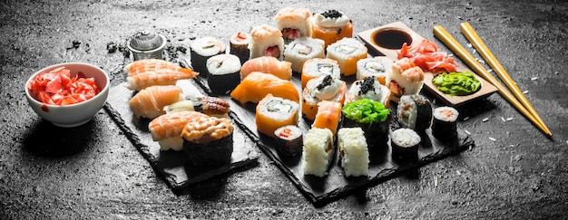 Diversi rotoli di sushi con le bacchette. sulla superficie rustica nera