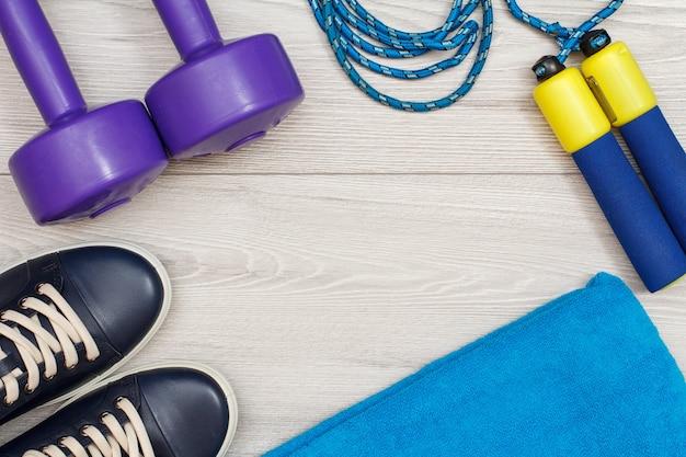 Diversi strumenti per il fitness in camera o in palestra sul pavimento grigio