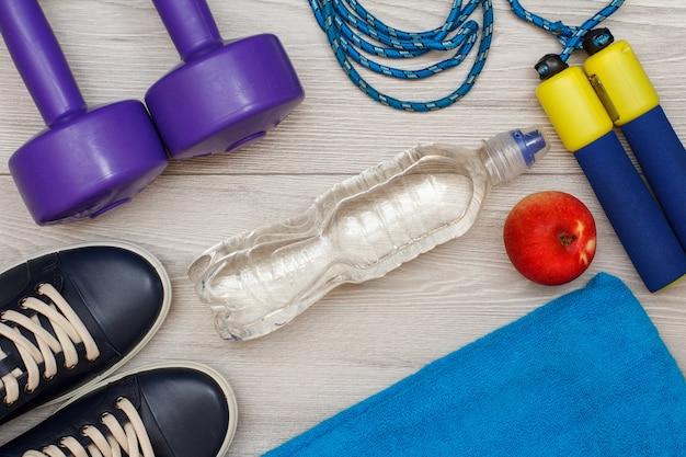 Diversi strumenti per il fitness con bottiglia d'acqua e mela in camera o in palestra su pavimento grigio