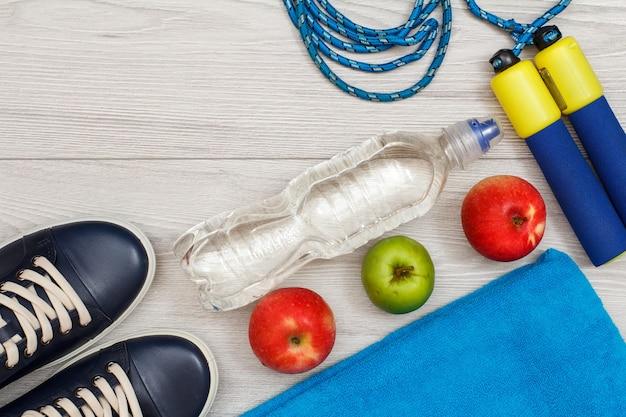 Diversi strumenti per il fitness con bottiglia d'acqua e mele in camera o in palestra su pavimento grigio